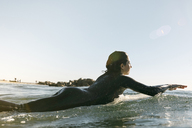 Side view of female surfer lying on surfboard in sea against clear sky - CAVF29418