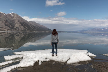 Woman standing on snow by river while looking at view against mountains and sky - CAVF29421