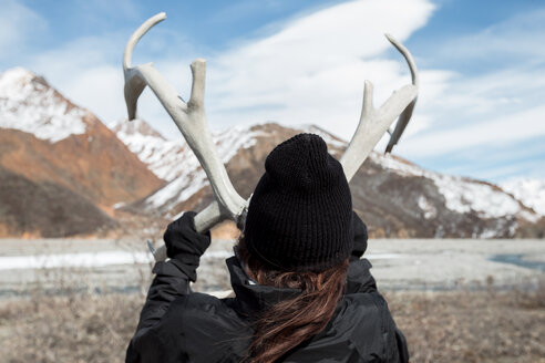Rear view of woman holding antlers against mountains at Denali National Park - CAVF29424