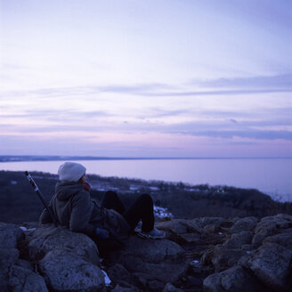 Woman sitting on stones and watching sea - FOLF01998