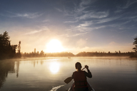 Rear view of woman traveling in boat on calm lake against sky - CAVF29596