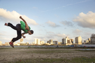 Full length of man performing stunt over field against sky - CAVF29647