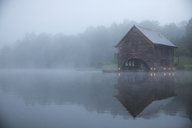 Symmetry view of log cabin by lake against trees during foggy weather - CAVF29730