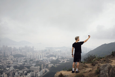 Man taking selfie while standing on rock by cityscape during foggy weather - CAVF29775