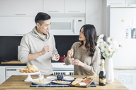 Happy couple looking at each other while having breakfast in kitchen - CAVF29793