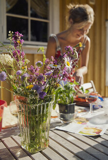 Bouquet of wildflowers with woman in background - FOLF02062