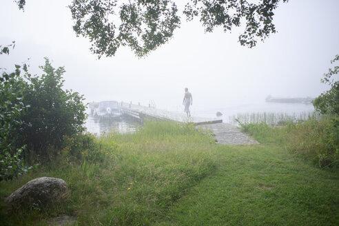 Rear view of man walking on jetty - FOLF02110