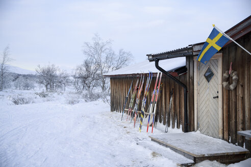 Skis leaning against wooden chalet in winter - FOLF02116