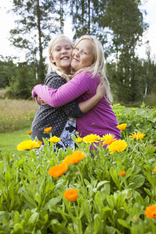 Two girls standing in yellow flowers and hugging - FOLF02152