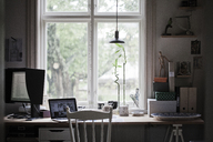 Desk with laptop and computer monitor by window - FOLF02239