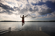 Rear view of man jumping into lake against cloudy sky - CAVF29886