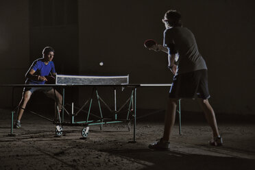 Friends playing table tennis against building at night - CAVF29898
