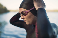 Close-up of female swimmer wearing swimming goggles at lakeshore - CAVF29982