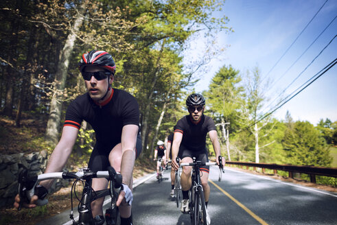Determined male cyclists riding bicycles on country road - CAVF29991