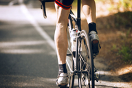 Low section of cyclist riding bicycle on road - CAVF30000