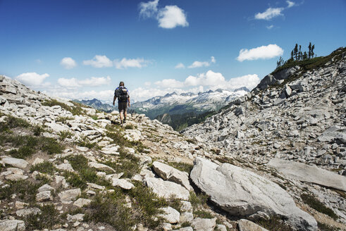Rear view of man hiking on mountain against sky - CAVF30045