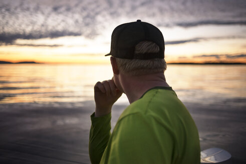 Side view of thoughtful man at Sucia Island during sunset - CAVF30090
