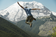 Rear view of man jumping against Mount Rainier - CAVF30099
