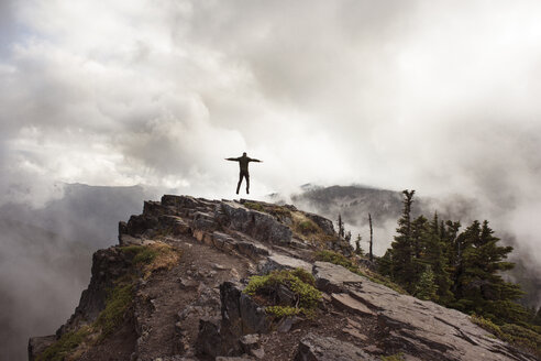 Man jumping on cliff against cloudy sky - CAVF30108