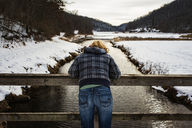 Rear view of woman leaning on railing over river during winter - CAVF30141
