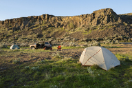 Tent on field by mountain at Gifford Pinchot National Forest with off-road vehicle in background - CAVF30168
