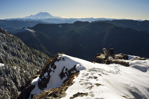 High angle view of man sitting with dog on snowcapped mountain - CAVF30183