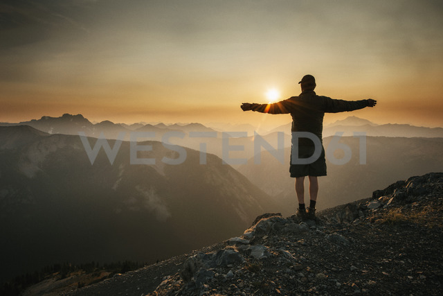 Rear view of man standing with arms outstretched on mountain against sky during sunset - CAVF30222 - Cavan Images/Westend61