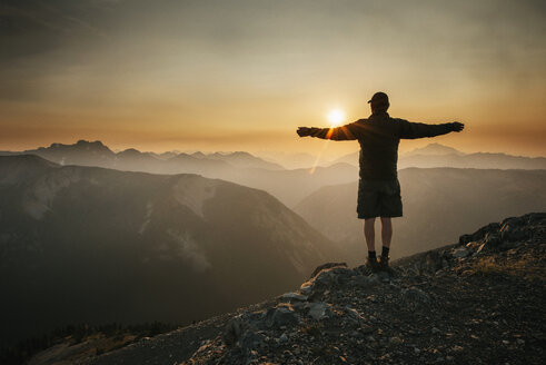 Rear view of man standing with arms outstretched on mountain against sky during sunset - CAVF30222