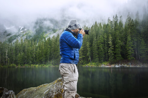 Side view of man photographing while standing against lake - CAVF30252