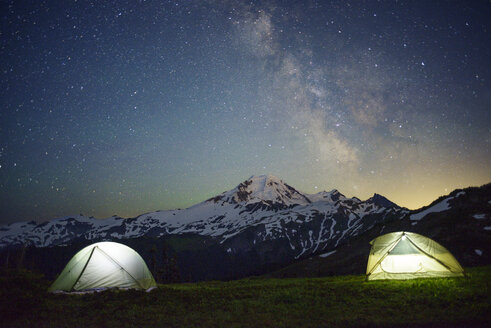 Illuminated tents on field against starry sky - CAVF30291