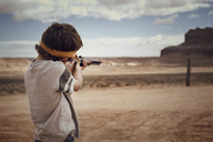 Boy aiming rifle while standing on field against sky - CAVF30297