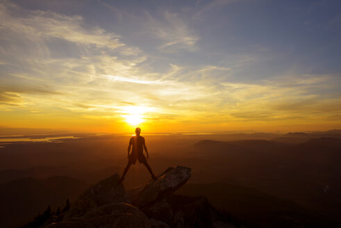Full length of hiker standing on top of mountain against sky during sunset - CAVF30333