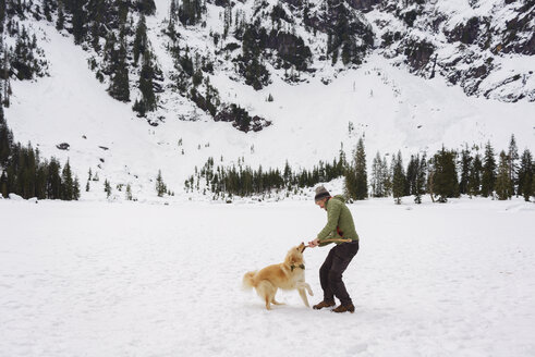 Happy man playing with Golden Retriever on snow covered field - CAVF30363