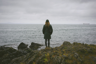 Rear view of woman standing on rocks by sea against cloudy sky - CAVF30369
