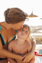 Mother embracing her daughter on beach - FOLF02305