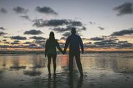 Rear view of couple holding hands while standing at Long Beach against cloudy sky - CAVF30403