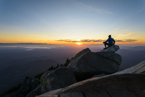 Man sitting on rock against sky at Mount Pilchuck State Park during sunset - CAVF30406