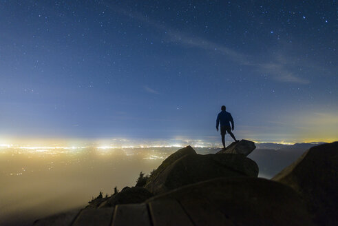 Silhouette man standing on rocks against star field at Mount Pilchuck State Park during night - CAVF30409