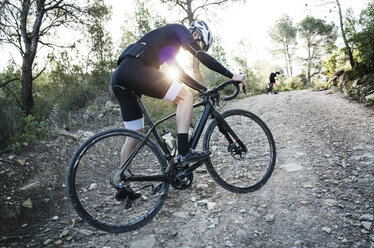 Side view of man cycling on dirt road - CAVF30457