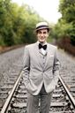 Portrait of man standing on railroad tracks - CAVF30499