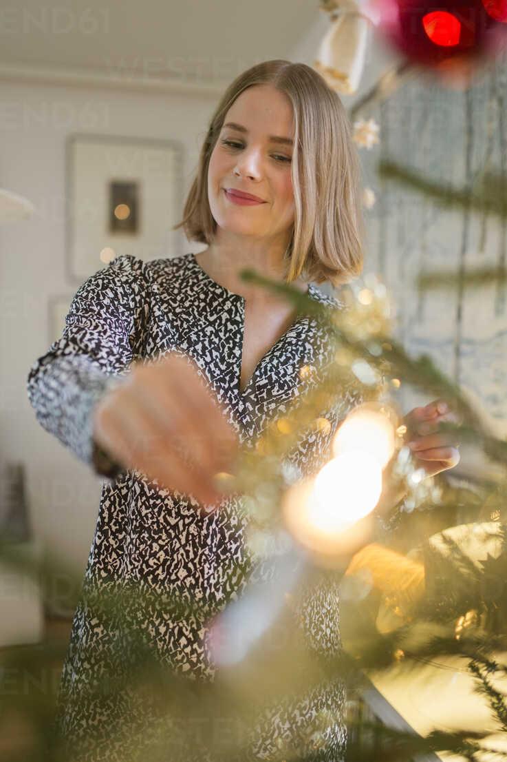 Young woman decorating Christmas tree - FOLF02566 - Jonne Heinonen/Westend61
