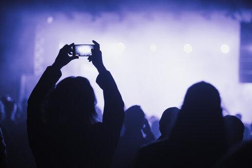 Woman using smart phone on concert - FOLF02581