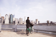 Businessman with bicycle enjoying city view from observation point - CAVF30570
