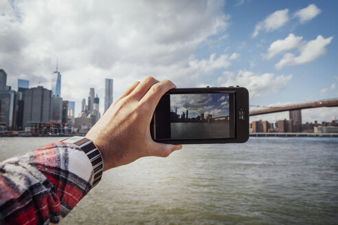 Cropped hand of man photographing skyline and Brooklyn Bridge - CAVF30573