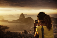 Rear view of woman photographing Guanabara Bay during sunset - CAVF30606