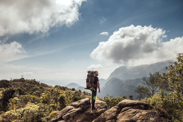 Side view of male backpacker standing on mountain against cloudy sky - CAVF30615