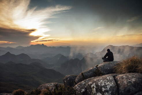 Rear view of man sitting on mountain during sunset - CAVF30618