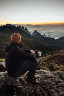 Side view of man holding mug while sitting on mountain during sunset - CAVF30621