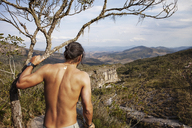 Rear view of shirtless man standing by tree on mountain - CAVF30633