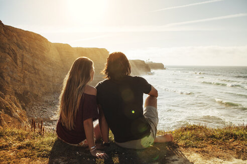 Rear view of couple sitting on cliff and looking at sea - CAVF30675